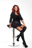 Redhead businesswoman sitting on a chair Stock Image