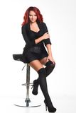 Redhead businesswoman sitting on a chair Stock Images