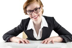 Redhead businesswoman sitting at desk typing Stock Image