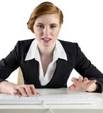 Redhead businesswoman sitting at desk typing Royalty Free Stock Photography