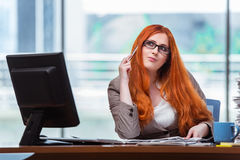 The redhead businesswoman sitting at her desk in the office Stock Photography
