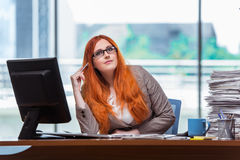 The redhead businesswoman sitting at her desk in the office Royalty Free Stock Photography