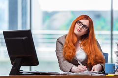 The redhead businesswoman sitting at her desk in the office Royalty Free Stock Photos