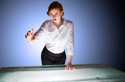 Redhead businesswoman standing and gesturing by a desk Royalty Free Stock Photography