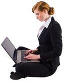 Redhead businesswoman using her laptop Stock Image