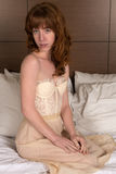 Redhead in bustier and skirt. Petite young Irish redhead in a cream bustier and skirt royalty free stock photo