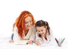 A redhead Caucasian mother and a little daughter drawing Royalty Free Stock Photography