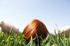 Redhead che risiede nell'erba che osserva in su Immagine Stock