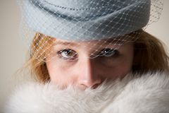 Redhead close-up in blue veiled hat and fur Royalty Free Stock Photos