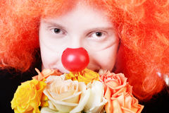 Redhead clown. Humble redhead clown with bunch of roses looking at us with kind smile Stock Photography