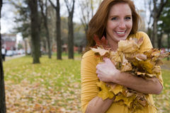 Redhead Collecting Leaves. A pretty caucasian redhead, 24, collects fallen leaves on a fall afternoon in New England, USA stock image