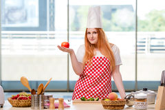 The redhead cook working in the kitchen royalty free stock photography