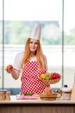 The redhead cook working in the kitchen Stock Photography