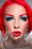Redhead covergirl. Close-up portrait of beautiful young redhead woman with fancy make-up and piercing Royalty Free Stock Photo