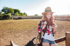 Redhead cowgirl using mobile phone while standing at ranch fence Royalty Free Stock Photography