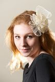 Redhead in cream fascinator and black top Stock Photos