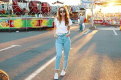 Redhead cute young hipster woman in stylish T-shirt in trendy sunglasses in blue jeans poses in an amusement park. On a background of bright sunset. Nice girl royalty free stock photo