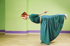 Redhead dancer in green dress Stock Photography