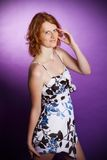 Redhead in a dress on a violet background. Beautiful redhead in dress posing in studio on a violet background Stock Photo