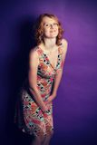 Redhead in a dress on a violet background. Beautiful redhead in dress posing in studio on a violet background Stock Image