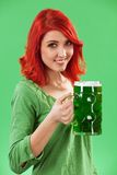 Redhead drinking green beer royalty free stock photography