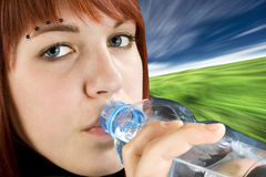 Redhead drinking water. Beautiful pierced redhead girl drinking water from a bottle. Studio shot stock photography