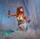 Redhead elf woman with a lantern in magical forest. Elf in magical winter forest with lantern Stock Photos