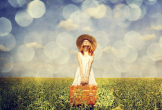 Redhead enchantress with suitcase at spring rapeseed field. Royalty Free Stock Photo