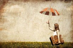 Redhead enchantress with umbrella and suitcase Royalty Free Stock Image
