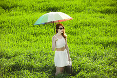 Redhead enchantress with umbrella and suitcase at spring country. Side Stock Photo