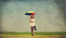 Redhead enchantress with umbrella and suitcase at spring country. Side Stock Image