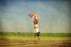 Redhead enchantress with umbrella and suitcase at spring country. Side Stock Photos