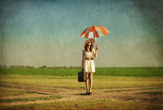 Redhead enchantress with umbrella and suitcase at spring country. Side Royalty Free Stock Photography