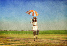 Redhead enchantress with umbrella and suitcase at spring country Stock Photos