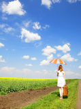 Redhead enchantress walking near rapeseed field. Stock Photography