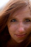 Redhead Face. Portrait of blue eyed 24 year old caucasian redhead woman on a windy afternoon in New England, USA royalty free stock images
