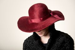 Redhead with face hidden by maroon hat Stock Photography