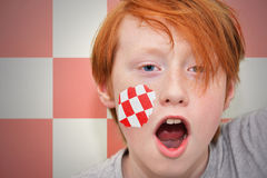 Redhead fan boy with abstract flag painted on his face Royalty Free Stock Photography