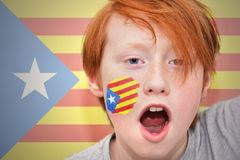 Redhead fan boy with catalan flag painted on his face. On the catalan flag background Stock Images