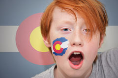 Redhead fan boy with colorado state flag painted on his face. On the colorado state flag background royalty free stock photo