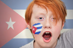 Redhead fan boy with cuban flag painted on his face. On the cuban flag background royalty free stock images