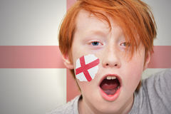 Redhead fan boy with english flag painted on his face. On the english flag background Stock Images