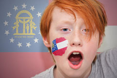 Redhead fan boy with georgia state flag painted on his face. Royalty Free Stock Photo