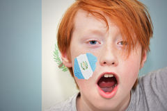 Redhead fan boy with guatemalan flag painted on his face Stock Image