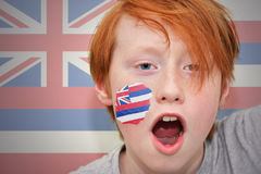 Redhead fan boy with hawaii state flag painted on his face. On the hawaii state flag background royalty free stock photo