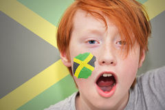 Redhead fan boy with jamaican flag painted on his face. On the jamaican flag background stock photo