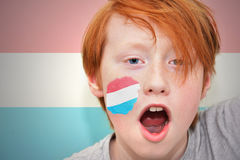Redhead fan boy with luxembourg flag painted on his face Royalty Free Stock Images