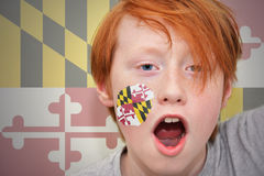 Redhead fan boy with maryland state flag painted on his face. On the maryland state flag background royalty free stock photos