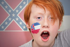 Redhead fan boy with mississippi state flag painted on his face. Royalty Free Stock Photography