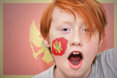 Redhead fan boy with montenegro flag painted on his face Stock Images